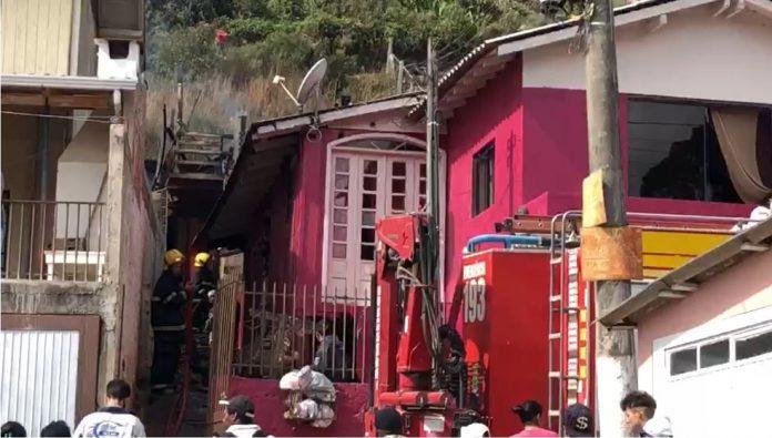 #Pracegover Na foto, fachada de uma residência atingida pelo fogo e o caminhão dos bombeiros