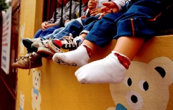 #Pracegover Na foto, crianças sentadas em um muro baixo