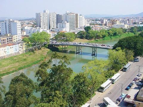 #Pracegover Na foto, imagem panorâmica da cidade: prédios, rio e árvores