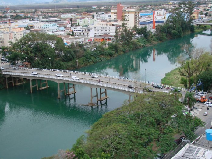 #Pracegover Foto: na imagem há um rio, uma ponte, árvores, construções e carros