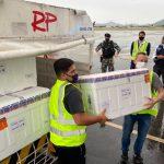 #Pracegover Na foto, homem carregam caixas com doses da vacina