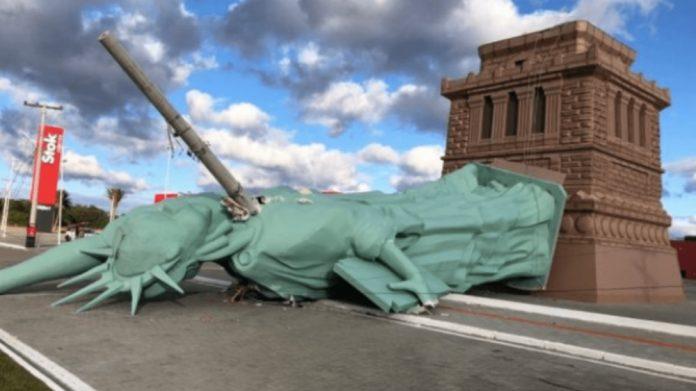 #Pracegover Na foto, estátua caída sobre um poste