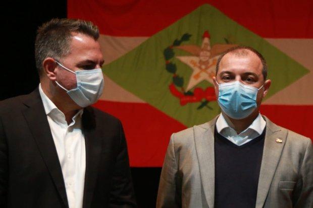 #Pracegover Foto: na imagem há dois homens de máscara e a bandeira de SC