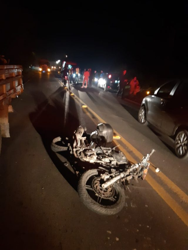 #Pracegover Foto: na imagem há uma motocicleta numa via, um carro, um caminhão e dezenas de pessoas no local