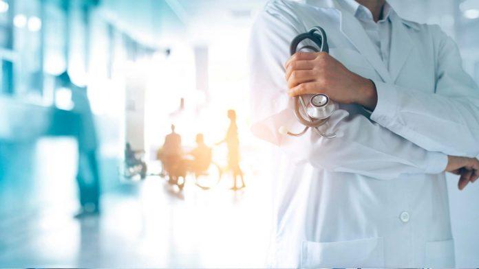 #Pracegover Na foto, médico usando jaleco e segurando um estetoscópio