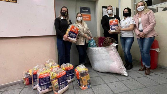 #Pracegover Na foto, pessoas com cobertores e cestas básicas