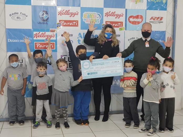 #Pracegover Foto: na imagem há dois adultos, algumas crianças e um cheque simbólico