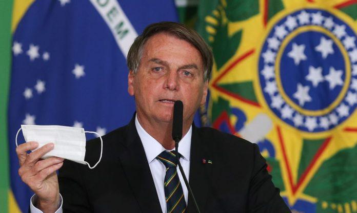 #Pracegover Na foto, Bolsonaro aparece segurando uma máscara
