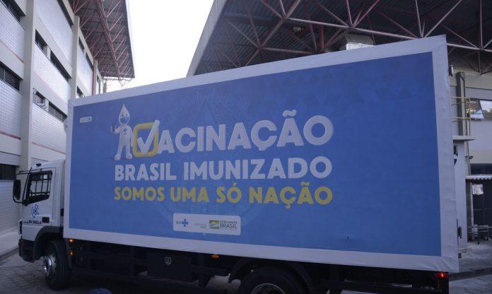 #Pracegover Foto: na imagem há um caminhão baú e duas edificações