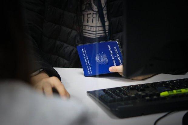 #Pracegover Foto: na imagem há uma mesa, um teclado, mãos, parte do corpo de uma pessoa e uma carteira de trabalho