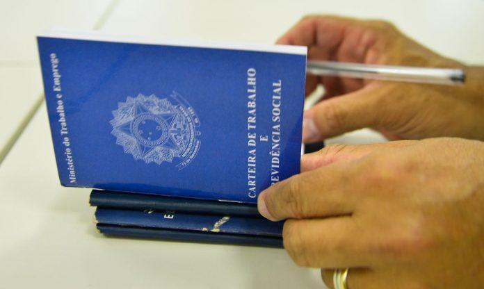 #Pracegover Foto: na imagem há carteiras de trabalho, mãos e uma caneta