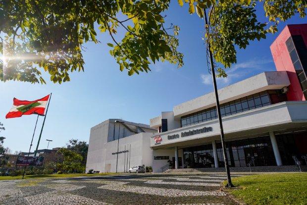 #Pracegover Foto: na imagem há um edifício, uma bandeira e árvores