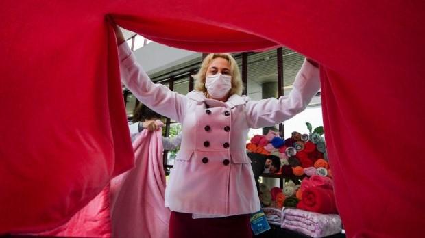 #Pracegover Na foto, mulher segura um cobertor vermelho