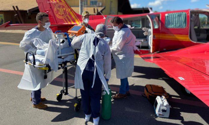 #Pracegover Foto: na imagem há profissionais de saúde, uma maca com aparelhos e uma aeronave