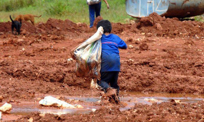 #Pracegover Foto: na imagem há uma criança e lama