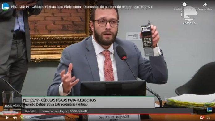 #Pracegover Na foto, deputado segura um celular antigo