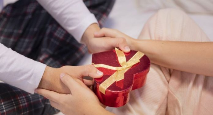 #Pracegover Foto: na imagem há um presente e quatro mãos