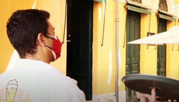 #Pracegover Na foto, garçom usando máscara