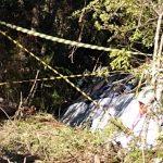 #Pracegover Na foto, micro-ônibus caído e preso pelas árvores