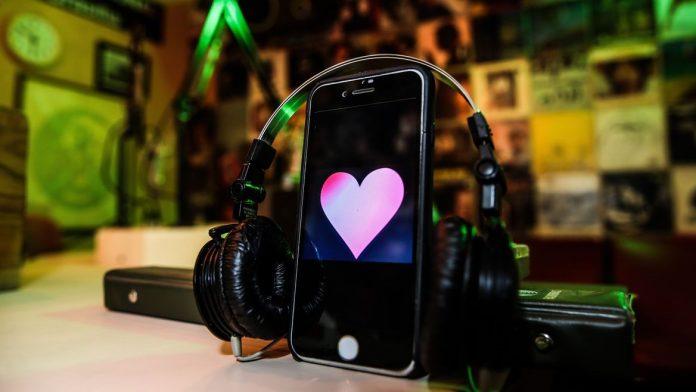 #Pracegover Na foto, celular com um coração na tela e uma fone de ouvido por cima