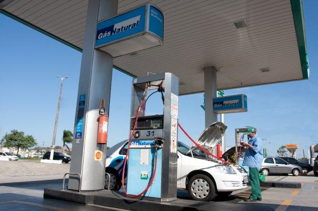 #Pracegover Foto: na imagem há um posto de gasolina, uma pessoa e um carro