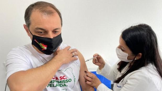 #Pracegover Na foto, Governador aparece recebendo vacina no braço