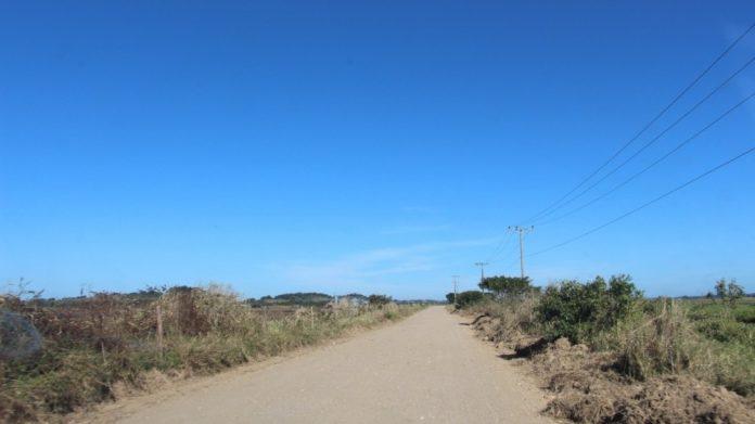 #Pracegover Na foto, estrada de chão e vegetação nas margens