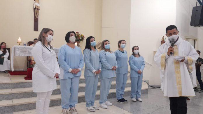 #Pracegover Foto: na imagem há profissionais de saúde, um celebrante e o altar de uma igreja