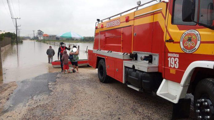 #Pracegover Na foto, caminhão do Bombeiros e pessoas saindo de um barco salva-vidas