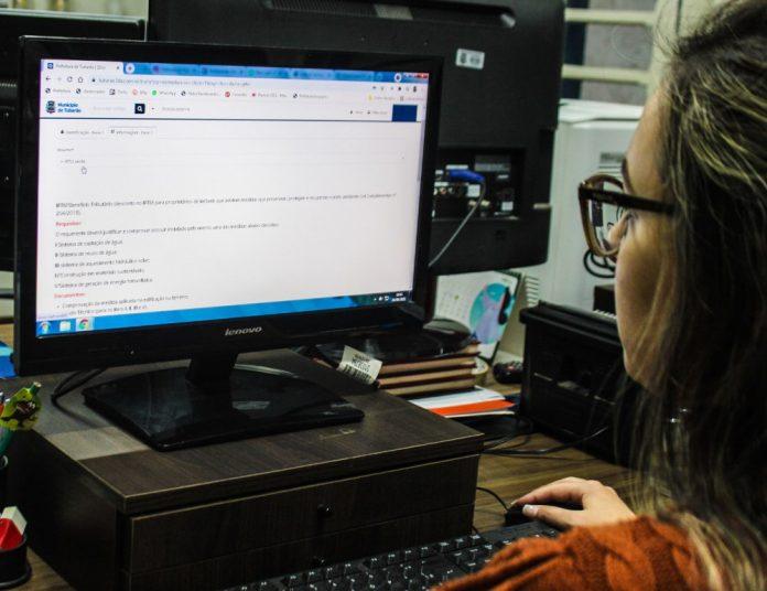 #Pracegover Na foto, mulher em frente a um computador
