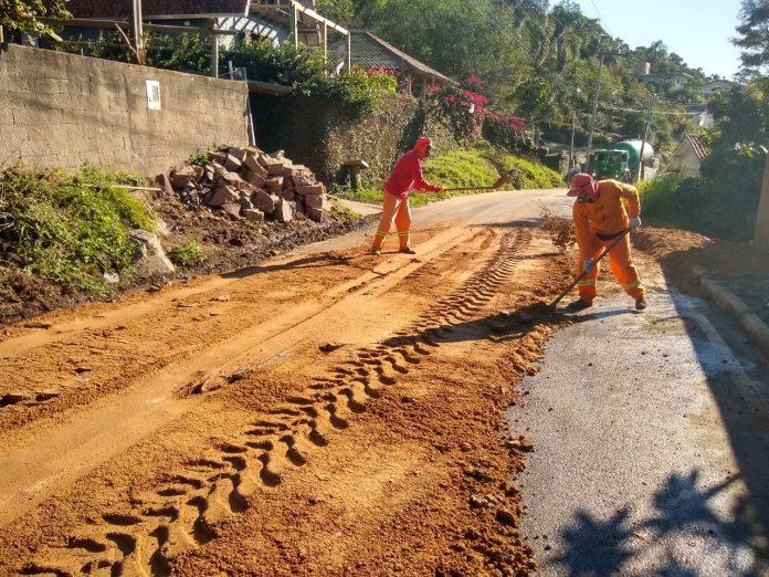 #Pracegover Foto: na imagem há dois homens, uma estrada, muro, pedras e árvores
