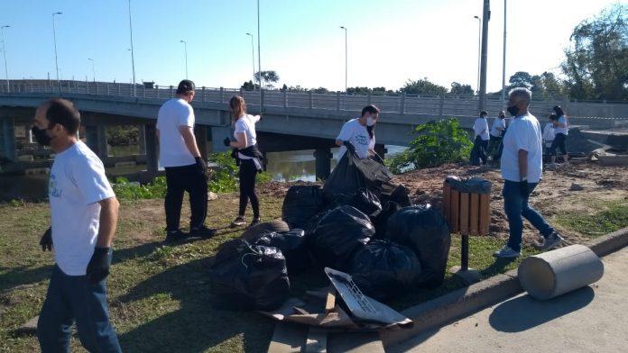 #Pracegover Foto: na imagem há pessoas, uma ponte, árvores e sacos de lixo