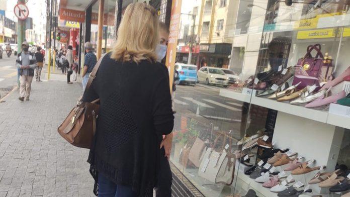 #Pracegover Na foto, mulheres olhando vitrine de calçados