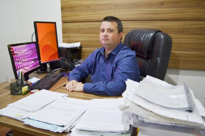 #Pracegover Foto: na imagem há um homem, papéis, computador, cadeira e uma mesa