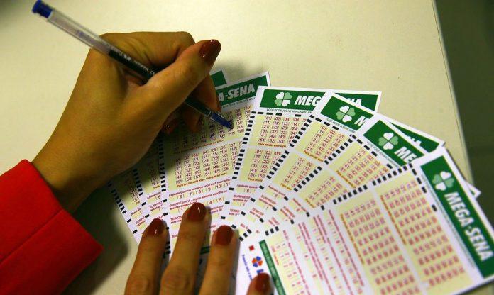 #Pracegover Na foto, mulher marca bilhetes de loteria