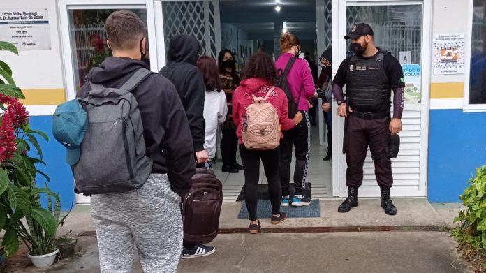 #Pracegover Na foto, alunos entrando em uma escola e um agente de segurança na porta