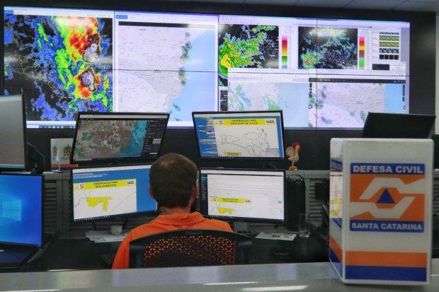 #Pracegover Foto: na imagem há uma pessoa e telas de computadores
