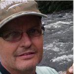 #Pracegover Na foto, Edenilson aparece sorrindo, usa óculo de grau e boné de cor clara