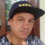 #Pracegover Na foto, Juliano aparece sério, usa boné preto, camiseta com estampa preto e branco e um colar