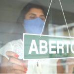 #Pracegover Foto: na imagem há uma mulher, uma placa e uma vitrine