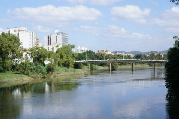 #Pracegover Na foto, rio Tubarão com águas claras, mata verde nas margens e ao fundo uma ponte
