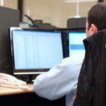 #Pracegover Foto: na imagem há computadores, um homem e um telefone