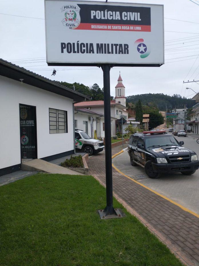 #Pracegover Foto: na imagem há veículos, construções, via e placa