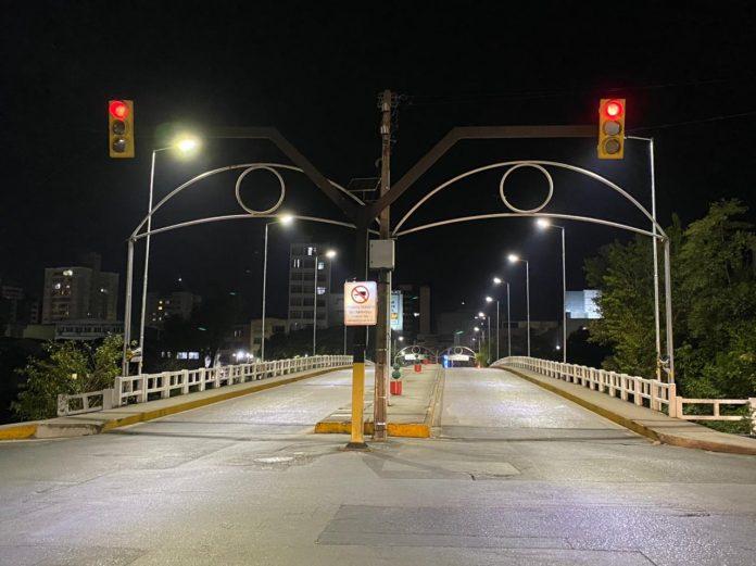 #Pracegover Foto: na imagem há semáforo, iluminação e ponte
