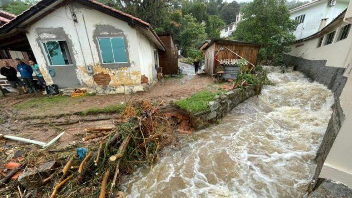 #Pracegover Na foto, água escorrendo em grande quantidade ao lado de uma casa