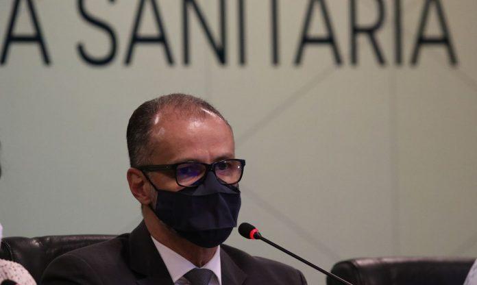 #Pracegover Foto: na imagem há um homem de terno e máscara e um microfone