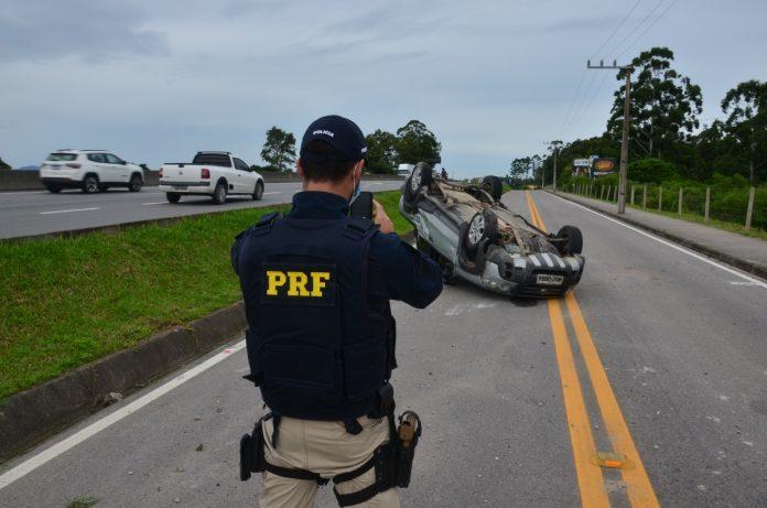 #Pracegover Foto: na imagem há um veículo virado, dois carros em uma via e um homem