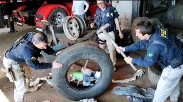 #Pracegover Na foto, policiais destroem um pneu para retirar drogas
