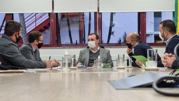 #Pracegover Foto: na imagem há pessoas, mesa, copos e folhas