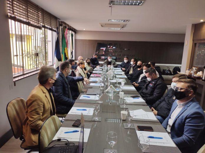 #Pracegover Foto: na imagem há pessoas, mesa, cadeiras, folhas, copos, canetas, bandeiras e celulares
